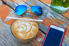 Kopp av den varma espressokaffedrinken med solglasögon och mobiltelefonen Royaltyfri Foto