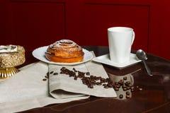 Kopp av den varma kaffe och bullen på den gamla trätabellen royaltyfri fotografi