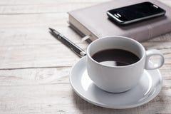 Kopp av den varma kaffe och dagboken på den wood tabellen Royaltyfri Foto