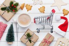 Kopp av den varma kakao, feriegarneringar, gåvan, gåva, granträdet och shoppingkorgen på den vita tabellen från över Planera för  royaltyfri bild