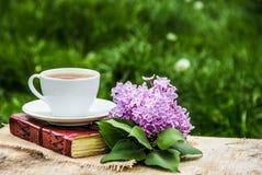 Kopp av den varma te, boken och filialen av lilan Trädgård för te på våren Hem- cosiness royaltyfri fotografi