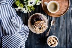 Kopp av donuts för coffe och för en choklad på svart trä royaltyfria bilder