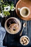 Kopp av donuts för coffe och för en choklad på svart trä royaltyfri bild
