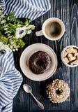 Kopp av donuts för coffe och för en choklad på svart trä royaltyfri foto