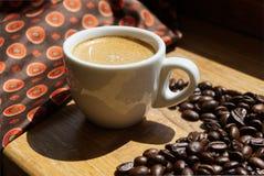 Kopp av espresso med kaffebönor på träbakgrund arkivfoto