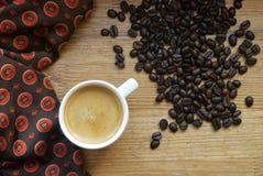 Kopp av espresso med kaffebönor på träbakgrund royaltyfri foto