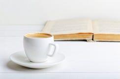 Kopp av espresso och boken Fotografering för Bildbyråer