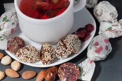 Kopp av jordgubbete med handgjorda godisar arkivbild