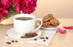 Kopp av kaffe, kakor, choklad och blommor royaltyfri foto
