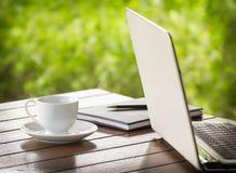 Kopp av kaffe och bärbar dator Fotografering för Bildbyråer