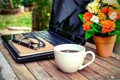 Kopp av kaffe och bärbar dator Arkivbild