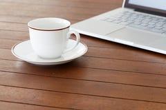 Kopp av kaffe och bärbar dator Arkivfoto