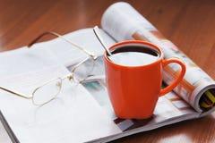 Kopp av kaffe och tidskriften Arkivfoton