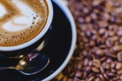 kopp av läckert kaffe med kaffebönor royaltyfri bild