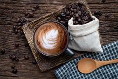 Kopp av lattekaffe med kaffekorn på trätabellen arkivbilder