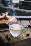 Kopp av ljust rödbrun te med citronen och farin på träbackgraund Varm drink för hostabot Traditionell medicin och naturligt honom royaltyfria bilder