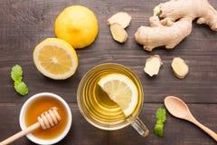 Kopp av ljust rödbrun te med citronen och honung på träbakgrund Arkivbild