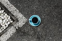 Kopp av mörkt kaffe på dengrå färger vägbanken med den vita orienteringen arkivbilder