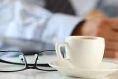 Kopp av morgonkaffe och exponeringsglas på worktablen Royaltyfria Foton