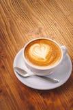 Kopp av nytt cappuccinokaffe på trätabellen royaltyfri fotografi