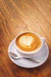 Kopp av nytt cappuccinokaffe på trätabellen royaltyfri bild