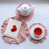 Kopp av parfymerat rosa te på att virka servetten, tekannan och kuvertet på fönsterbräda red steg Romansk bra morgon royaltyfri foto