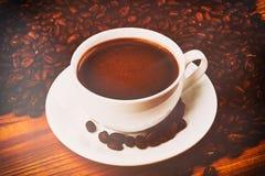 kopp av smakligt kaffe, på lantlig trätabellbakgrund royaltyfria bilder