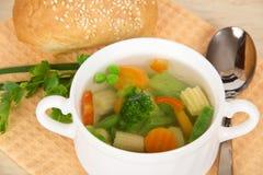 Kopp av soppa och bröd för ny grönsak Arkivfoton