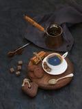 Kopp av svart kaffe med chokladkex, kanelbruna pinnar och kuber för rottingsocker på lantligt träbräde över den mörka stenen Royaltyfri Fotografi