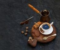 Kopp av svart kaffe med chokladkex, kanelbruna pinnar och kuber för rottingsocker på lantligt träbräde över den mörka stenen Arkivbilder