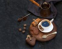 Kopp av svart kaffe med chokladkex, kanelbruna pinnar och kuber för rottingsocker på lantligt träbräde över den mörka stenen Royaltyfria Foton