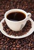 Kopp av svart kaffe med kaffebönor omkring Fotografering för Bildbyråer