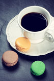 Kopp av svart kaffe med makron royaltyfria foton