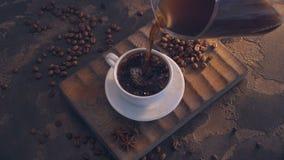 Kopp av svart kaffe och bönor över grungeträtabellen lager videofilmer