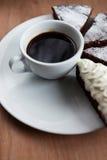 Kopp av svart kaffe och chokladkakan Arkivbilder