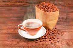 Kopp av svart kaffe och kaffebönor i en påse på träbackgrou Arkivbild