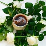 Kopp av svart kaffe och vita rosor, på vit träbakgrund Arkivfoto