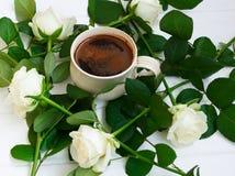 Kopp av svart kaffe och vita rosor, på vit träbakgrund Royaltyfria Foton