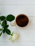 Kopp av svart kaffe och vita rosor, på vit träbakgrund Arkivbilder