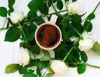 Kopp av svart kaffe och vita rosor, på vit träbakgrund Arkivfoton
