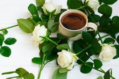 Kopp av svart kaffe och vita rosor, på vit träbakgrund Royaltyfria Bilder