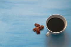 Kopp av svart kaffe på blå träbakgrund med sunda mellanmål - muttrar Pecannöt och kopp kaffe royaltyfri fotografi
