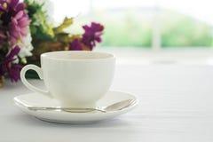 Kopp av svart kaffe som förläggas på den vita tabellblomman och oskarpa gard Arkivfoto