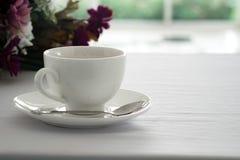 Kopp av svart kaffe som förläggas på den vita tabellblomman och oskarpa gard Royaltyfri Foto