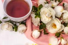 Kopp av svart te med rosa höfter för vita blommor på en vit bakgrund royaltyfri foto