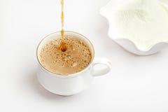 Kopp av tea med mejerimjölkpulver arkivbild