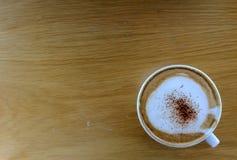 Kopp av varm cappuccino på trätabellen Royaltyfri Bild