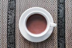 Kopp av varm choklad eller kakao på plattan arkivfoto