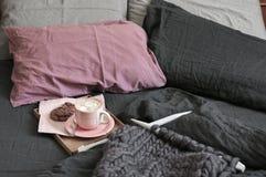 Kopp av varm choklad med kakor och klumpigt handarbete i säng royaltyfri fotografi