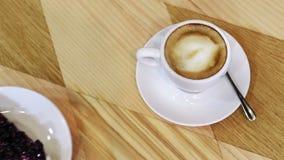 Kopp av varm kaffe och ostkaka med vinbäret på a stock video
